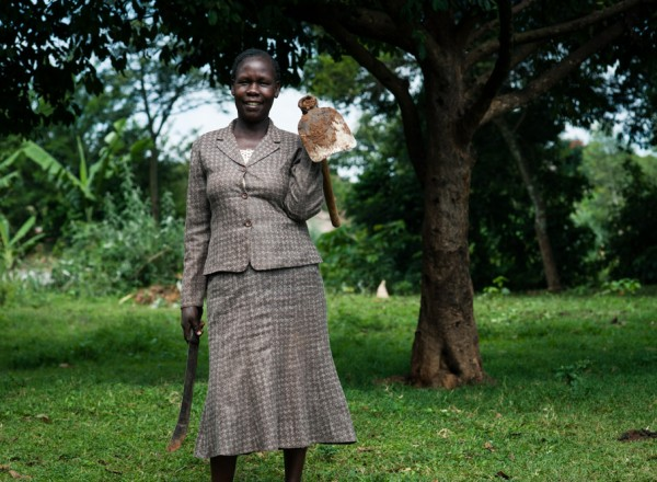 Anne holds the two tools she uses most often when farming: a machete, known in Kenya as a panga, and a short hoe called a jembe.  Photo: Hailey Tucker